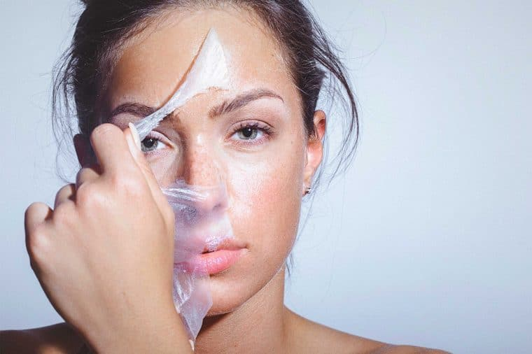 Lady peeling off face mask with large pores